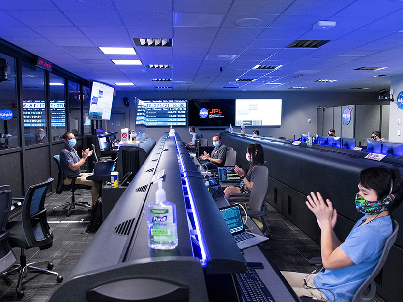 A NASA mission control room sparsely staffed with masked scientists