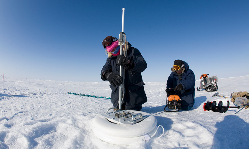 Two scientists measure snow and ice in the Arctic