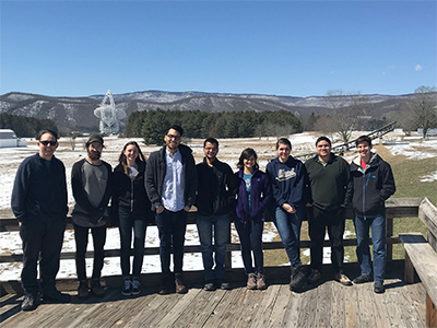 Nine people stand in a line on a wooden deck with a radio telescope and snowy mountains in the background