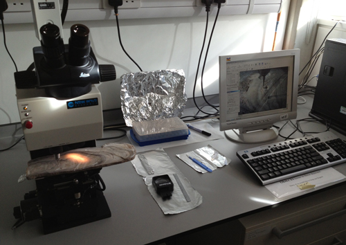 Lab bench with a computer and an instrument used to drill small samples from speleothems