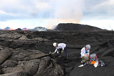 A researcher in a white shirt and hiking boots hammers at a field of freshly formed volcanic rock to collect a sample; another researcher takes notes nearby.