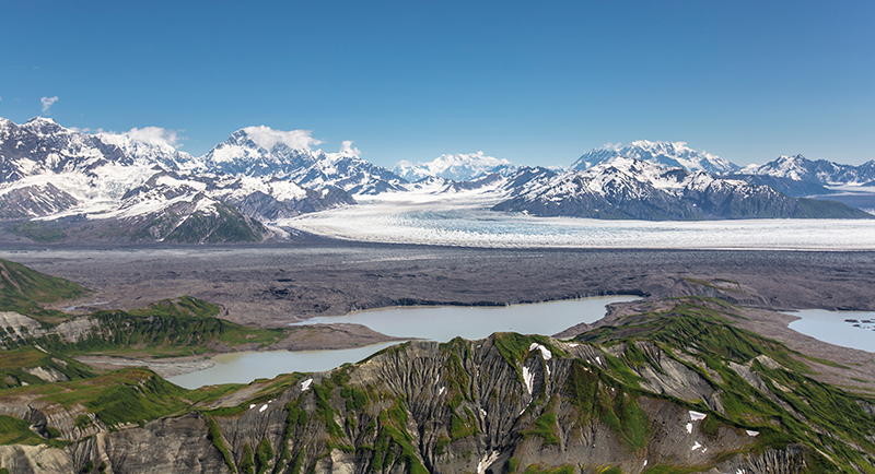 Two glaciers and a glacial lake with mountains in the background