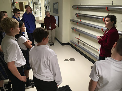 Middle school students in a college hallway looking at ice cores