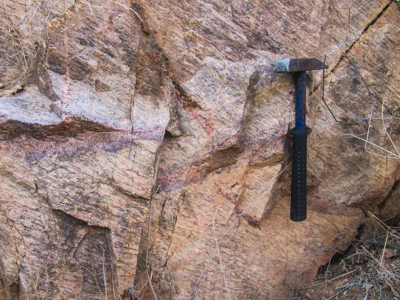 Close up of an outcrop of pink cratonic rock with a rock hammer for scale