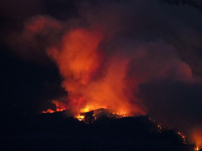 The CZU Lightning Complex Fire burns in the Santa Cruz Mountains, lighting up the night sky.