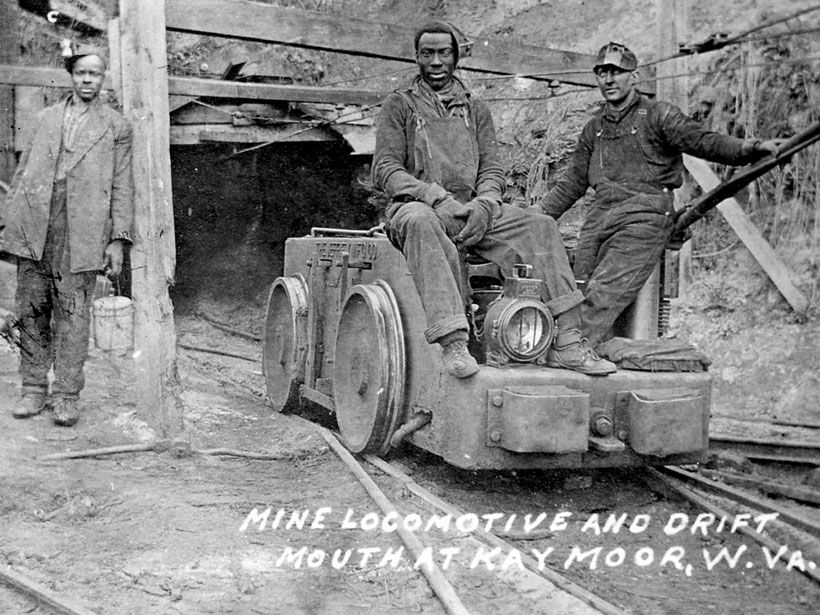 Black-and-white photo of miners and a mine locomotive in Kaymoor, W.Va.