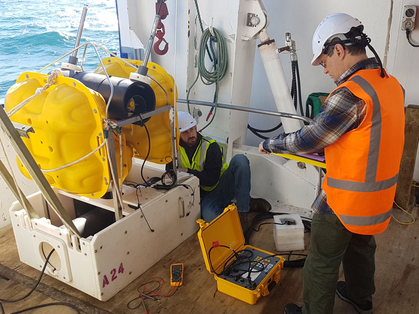 Two people check instrumentation on the deck of a research vessel at sea