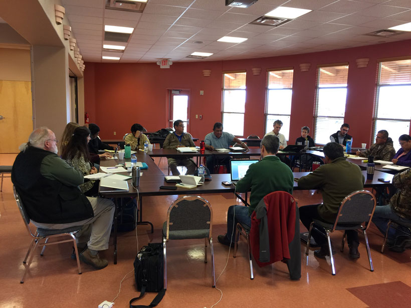 Scientists and tribal members gather round a table to discuss cultural traditions.