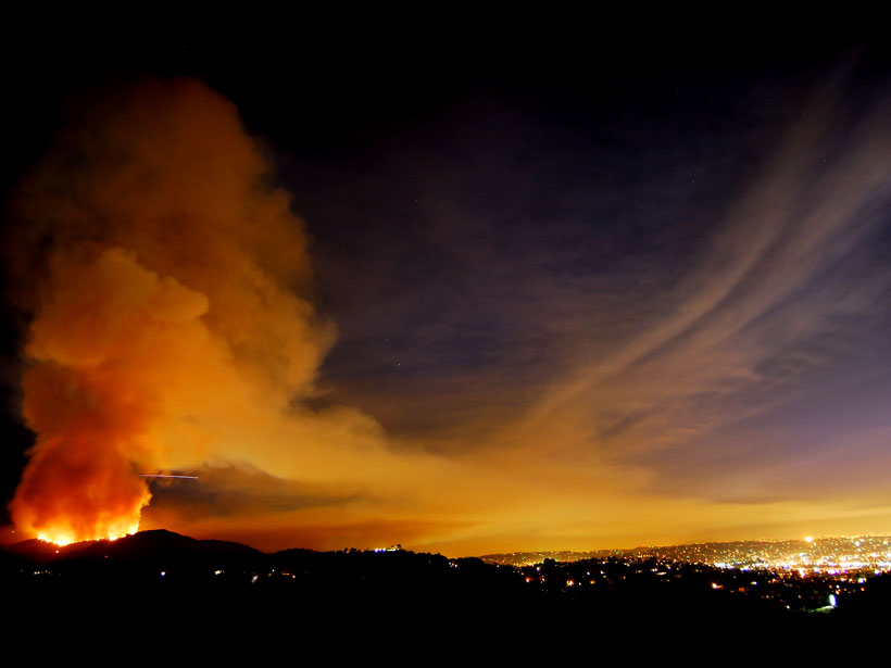 Smoke and fire rise from a hilltop at night and blow toward Hollywood, Calif., the lights of which are visible at right.