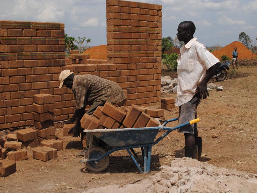 Two men construct a mud-brick shelter for landslide victims in Uganda.