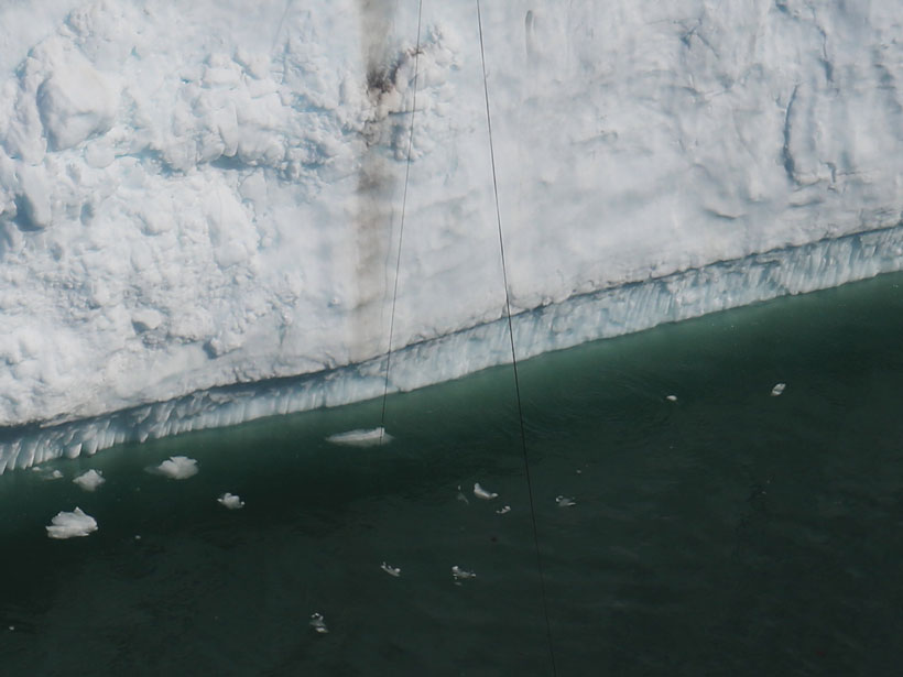 A cable hanging off an ice cliff being pulled by water currents