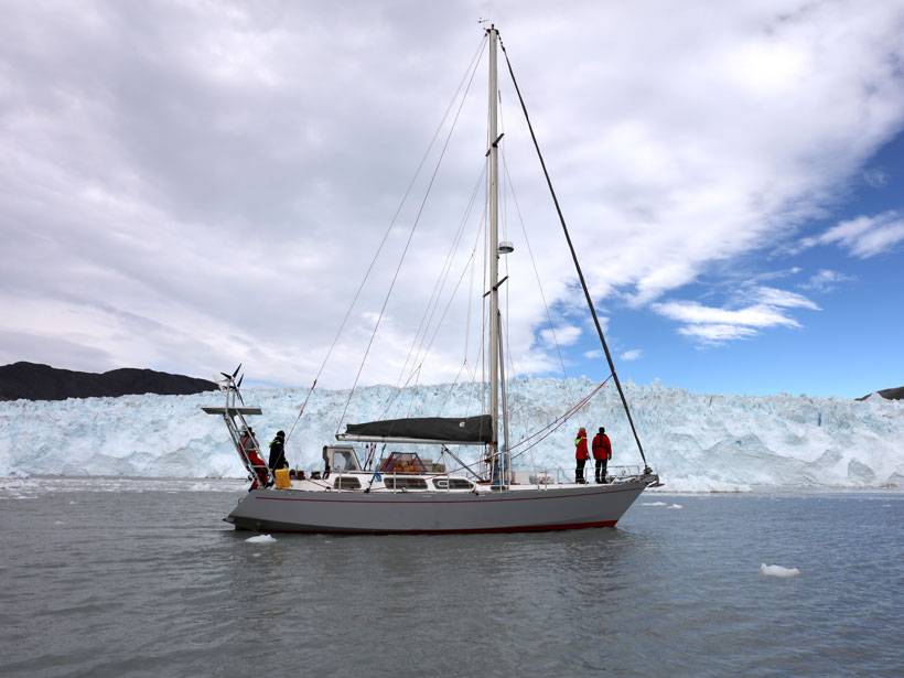 Exiles sails past a glacier with the crew on deck.