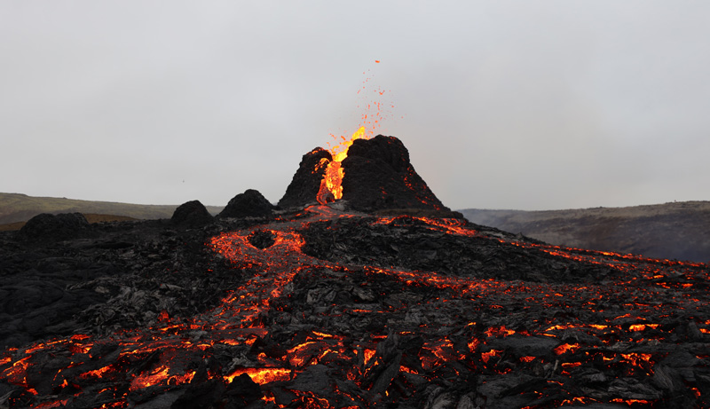 Against a gray sky, orange lava pours and pops out of Fagradalsfjall in Iceland on the second day of the eruption. In the foreground, cooling lava glows against the black basalt that's already solidified.
