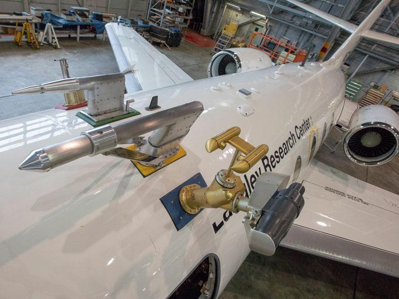 Close up of specialized sampling instruments atop a NASA aircraft in a hangar