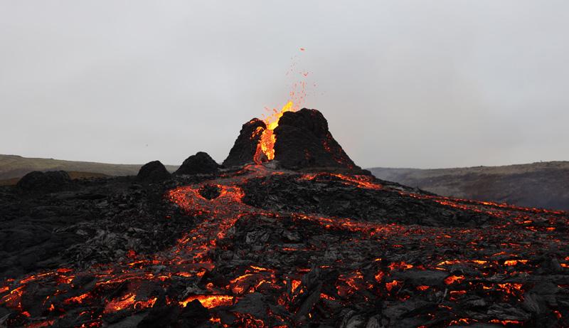 En contra de un cielo gris, lava naranja sale del Fagradalsfjall en el segundo día de la erupción. Al frente, lava enfriándose brilla en contraste con el basalto negro que ya está solidificado.