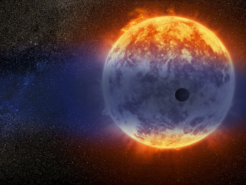 The silhouette of an exoplanet is seen in front of a red dwarf star in this artist's representation.
