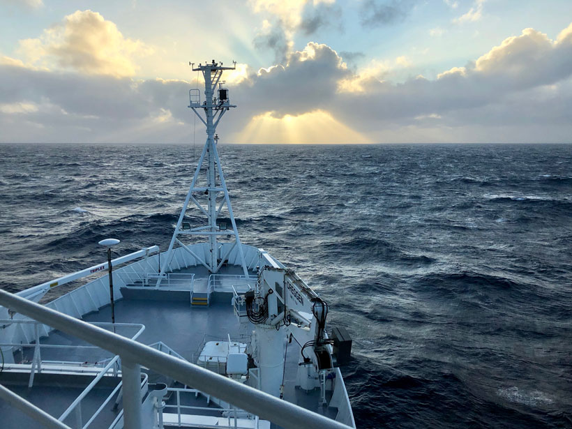 View over the bow of a ship across the ocean and toward a partly cloudy horizon