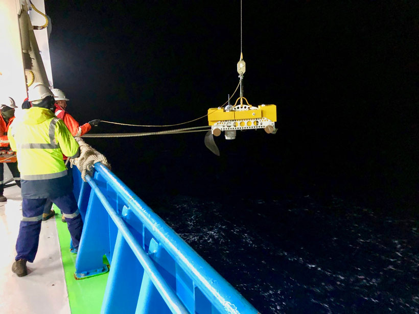 Crewmembers help lower an instrument into the water off the side of a ship