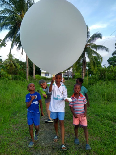 Students in Nuquí, Chocó, Colombia, prepare to launch a sonde balloon during the fieldwork campaign.