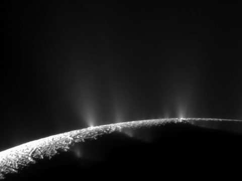 Black-and-white image of plumes erupting from the surface of Saturn's moon Enceladus