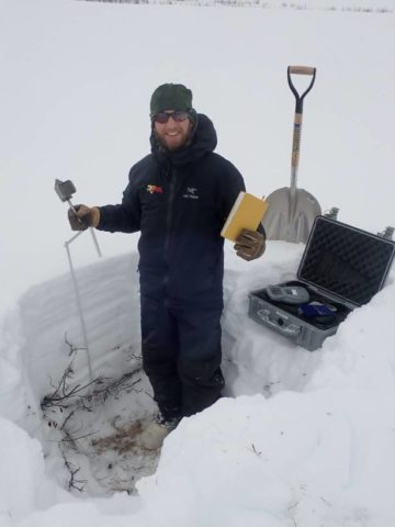A researcher holding research tools in a snow pit.