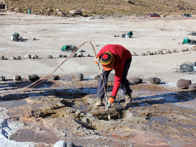 A scientist bends over to insert a pole equipped with sensors into a geyser.