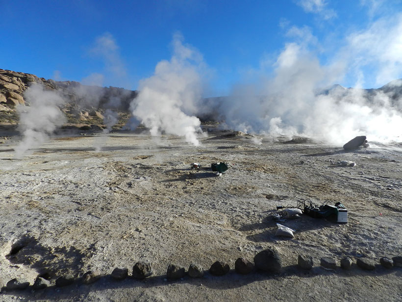 Scientific instruments sit in the foreground while steam rises from several geysers in the background.