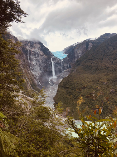 Waterfalls pouring from a distant glacier run down a valley toward a mountain lake.