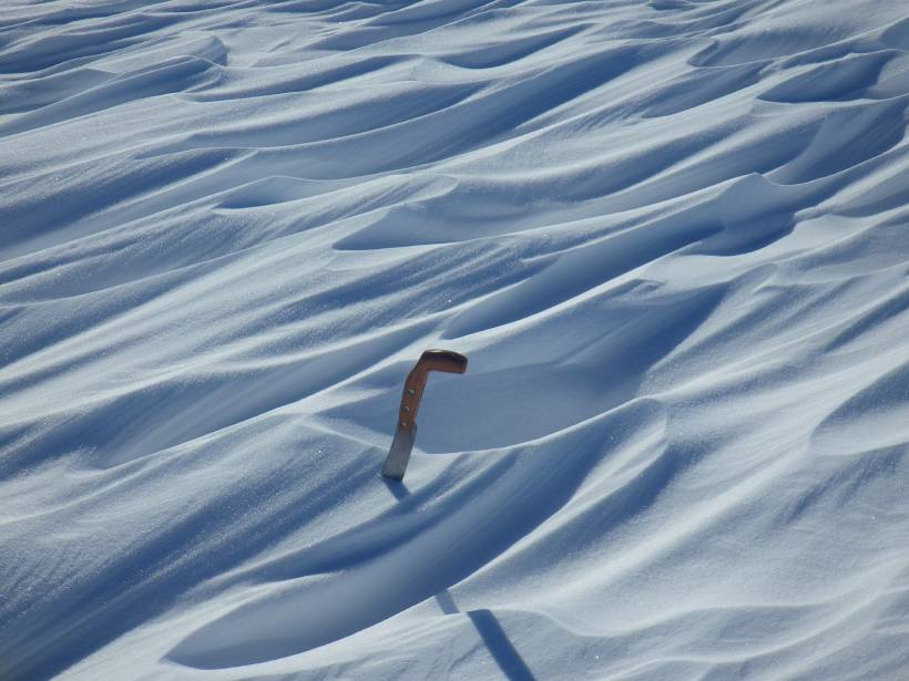 Snow ridges shaped by polar wind, with a knife embedded in the ridge for scale
