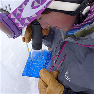 Researcher Kelsey Dean stands in a snow pit while using a macroscope to examine ice crystals on a blue slide.