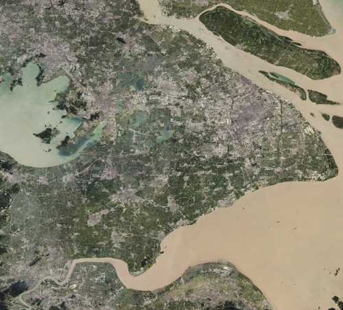 A satellite view of Shanghai and the Yangtze River delta, showing expansive urban development
