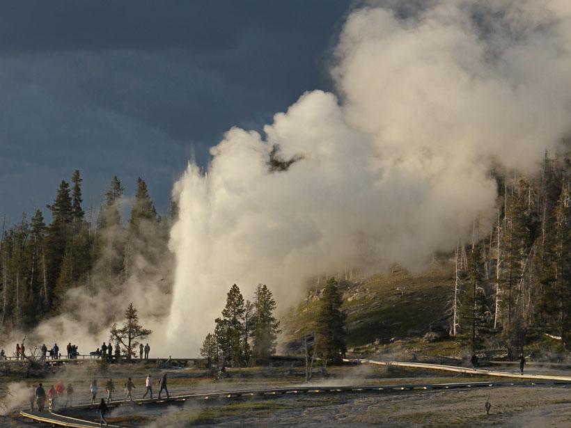 Visitors walking on a boardwalk watch a geyser erupt.