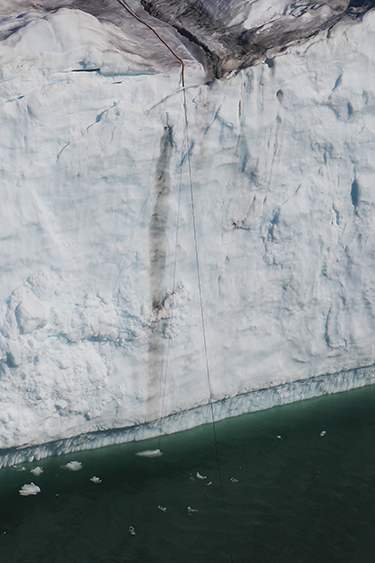 A narrow cord extends over the edge of a tall glacial ice cliff into the water below
