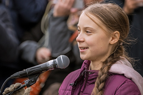 Climate activist Greta Thunberg, a teenage girl with braided, long brown hair, speaks in front of a crowd at a climate strike. She wears a purple winter coat and brown gloves and faces left while speaking into a microphone.