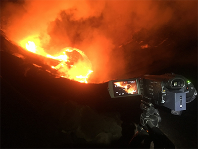 A video camera (foreground) stands above a glowing orange lava lake
