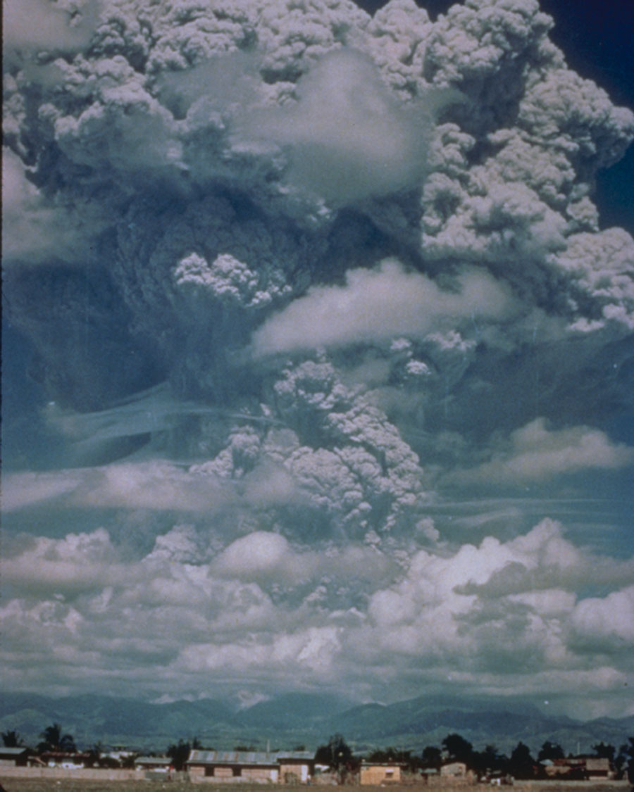 View from ground level of an enormous volcanic plume erupting into the sky