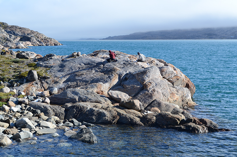 Geologists work atop a coastal rock outcrop