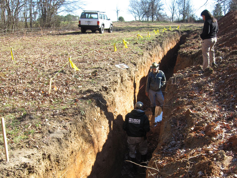 Two people stand in a deep trench in the soil while a third person stands above the trench.