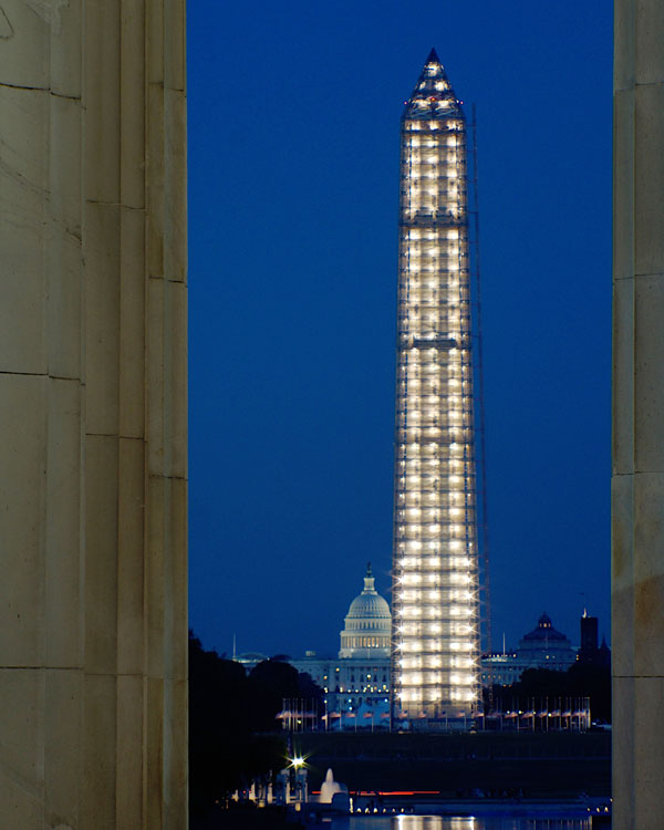 A nighttime view of the Washington Monument surrounded by scaffolding.